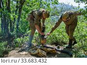 Солдаты на природе пытаются растопить самовар сапогом (2016 год). Редакционное фото, фотограф Андрей Мигелев / Фотобанк Лори