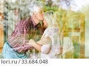 Senior gibt seiner Ehefrau einen Kuss auf die Stirn als Zeichen der Liebe und Nähe. Стоковое фото, фотограф Zoonar.com/Robert Kneschke / age Fotostock / Фотобанк Лори