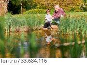 Купить «Großvater und Enkelsohn mit Angel beim Angeln zusammen am See im Sommer», фото № 33684116, снято 25 мая 2020 г. (c) age Fotostock / Фотобанк Лори
