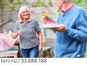 Senioren Paar auf einem Sommerfest feiert mit Sekt und Kuchen im Garten. Стоковое фото, фотограф Zoonar.com/Robert Kneschke / age Fotostock / Фотобанк Лори