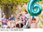 Junge als Geburtstagskind hält Luftballon mit der Neun mit Familie im Hintergrund. Стоковое фото, фотограф Zoonar.com/Robert Kneschke / age Fotostock / Фотобанк Лори