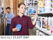 Купить «Woman is choosing with paint for repair», фото № 33697844, снято 16 февраля 2018 г. (c) Яков Филимонов / Фотобанк Лори