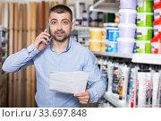 Купить «designer is choosing paint and talking by phone», фото № 33697848, снято 16 февраля 2018 г. (c) Яков Филимонов / Фотобанк Лори