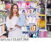 Купить «Young woman holding bottle of rinse aid», фото № 33697964, снято 19 октября 2019 г. (c) Яков Филимонов / Фотобанк Лори