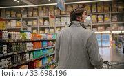 Купить «Young man in protective mask walking between different sections in the big grocery shop», видеоролик № 33698196, снято 25 мая 2020 г. (c) Константин Шишкин / Фотобанк Лори