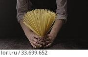 Купить «Female hands holding raw spaghetti pasta as a bouquet on a wooden table on a black background. Slow motion, Full HD video, 240fps, 1080p.», видеоролик № 33699652, снято 31 августа 2018 г. (c) Ярослав Данильченко / Фотобанк Лори