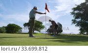 Купить «Caucasian male golfers playing on a golf course on a sunny day», видеоролик № 33699812, снято 4 ноября 2019 г. (c) Wavebreak Media / Фотобанк Лори