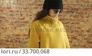 Купить « Caucasian woman showing her outfit on a brick wall», видеоролик № 33700068, снято 23 июля 2019 г. (c) Wavebreak Media / Фотобанк Лори