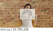 Купить «Caucasian woman holding a white rectangle on a brick wall», видеоролик № 33700208, снято 23 июля 2019 г. (c) Wavebreak Media / Фотобанк Лори