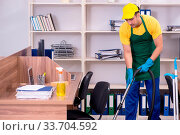 Купить «The young male contractor cleaning the office», фото № 33704592, снято 25 мая 2020 г. (c) easy Fotostock / Фотобанк Лори