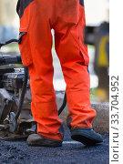 Купить «Construction workers during asphalting road works wearing coveralls. Manual labor on construction site», фото № 33704952, снято 6 июня 2020 г. (c) Matej Kastelic / Фотобанк Лори