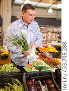 Купить «Adult man is choosing green onion in the store», фото № 33705288, снято 9 октября 2019 г. (c) Яков Филимонов / Фотобанк Лори