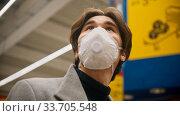 Купить «Young man in protective mask looking around in the grocery shop», фото № 33705548, снято 3 июля 2020 г. (c) Константин Шишкин / Фотобанк Лори