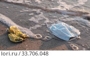 Close-up of used disposable face mask and plastic bag on the sandy beach in surf zone. Coronavirus (COVID-19) is contributing to pollution Seas and Oceans. Ecological pollution problem. Стоковое видео, видеограф Некрасов Андрей / Фотобанк Лори
