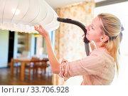Haushaltshilfe oder Reinigungskraft beim Staubsaugen an einer Lampe zu Hause. Стоковое фото, фотограф Zoonar.com/Robert Kneschke / age Fotostock / Фотобанк Лори