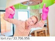 Putzfrau oder Reinigungskraft beim Lampe putzen beim Hausputz in der Wohnung. Стоковое фото, фотограф Zoonar.com/Robert Kneschke / age Fotostock / Фотобанк Лори