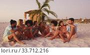 Friends sitting side by side on the beach. Стоковое видео, агентство Wavebreak Media / Фотобанк Лори