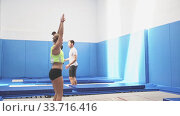 Group of active friends practicing and jumping in trampoline center. Стоковое видео, видеограф Яков Филимонов / Фотобанк Лори