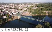 Купить «View from drone of small French town of Marmande with suspension bridge over Garonne river on summer day», видеоролик № 33716432, снято 18 июля 2019 г. (c) Яков Филимонов / Фотобанк Лори