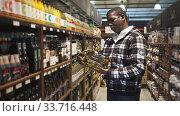 Купить «African American man making purchases in store, choosing vegetable oil», видеоролик № 33716448, снято 30 июня 2020 г. (c) Яков Филимонов / Фотобанк Лори