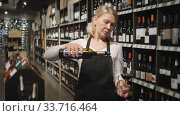 Confident mature female winemaker holding glass of wine, checking it in wine store. Стоковое видео, видеограф Яков Филимонов / Фотобанк Лори