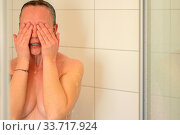 Купить «Naked woman having a shower rinsing her face under running water covering her eyes and breasts with her hands and arms in close up in a personal hygiene concept», фото № 33717924, снято 5 июня 2020 г. (c) easy Fotostock / Фотобанк Лори