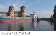 Купить «Грузовое судно проходит узкий пролив у средневековой крепости Олавинлинна. Савонлинна, Финляндия», видеоролик № 33719184, снято 24 июля 2018 г. (c) Виктор Карасев / Фотобанк Лори