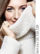 Blonde young beautiful woman dressed in white woolen sweater . Стоковое фото, фотограф Serg Zastavkin / Фотобанк Лори