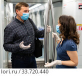 Man and woman in medical masks chatting in subway car. Стоковое фото, фотограф Яков Филимонов / Фотобанк Лори