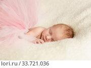 Маленькая новорожденная девочка спит на белом одеяле в розовой юбке-пачке из фатина. Стоковое фото, фотограф Наталья Гармашева / Фотобанк Лори