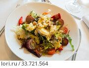 Купить «Salad with goat cheese, cherry tomatoes, arugula, nuts and raisins», фото № 33721564, снято 26 мая 2020 г. (c) Яков Филимонов / Фотобанк Лори