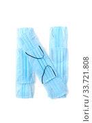 Купить «Letter N made from protective medical masks on a white background.», фото № 33721808, снято 2 мая 2020 г. (c) Ярослав Данильченко / Фотобанк Лори