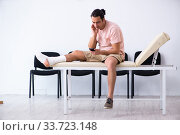 Купить «Young injured man waiting for his turn in hospital hall», фото № 33723148, снято 3 мая 2019 г. (c) Elnur / Фотобанк Лори