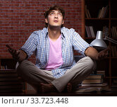 Купить «Young handsome student preparing for exams at night», фото № 33723448, снято 28 августа 2018 г. (c) Elnur / Фотобанк Лори