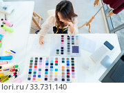 Купить «Top view a young adult fashion designer drawing and sketching her work at her atelier studio with colour palette as sole owner. Using for entrepreneur startup concept.», фото № 33731140, снято 11 июля 2020 г. (c) easy Fotostock / Фотобанк Лори
