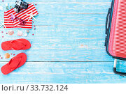 Купить «Red Summer background with camera starfish sandle sunglasses and Luggage on blue wooden table background with copy space», фото № 33732124, снято 3 июля 2020 г. (c) easy Fotostock / Фотобанк Лори