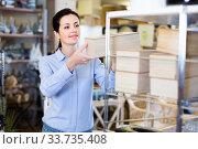 Купить «Woman standing with wooden box in decoration and furniture store», фото № 33735408, снято 22 ноября 2017 г. (c) Яков Филимонов / Фотобанк Лори