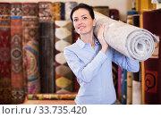 Female keep in hand colored carpet in interior shop. Стоковое фото, фотограф Яков Филимонов / Фотобанк Лори