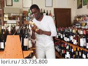 Купить «African American searching bottle of good wine», фото № 33735800, снято 1 августа 2019 г. (c) Яков Филимонов / Фотобанк Лори