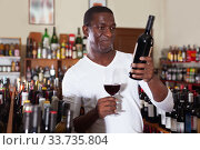 Купить «Confident african american male winemaker inspecting quality of red wine, checking it in wine store», фото № 33735804, снято 1 августа 2019 г. (c) Яков Филимонов / Фотобанк Лори