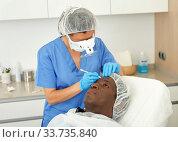 Купить «Cosmetician female in mask is preparing client for mesotherapy», фото № 33735840, снято 30 марта 2019 г. (c) Яков Филимонов / Фотобанк Лори