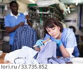 Купить «Woman dry cleaning clothes in laundry», фото № 33735852, снято 15 января 2019 г. (c) Яков Филимонов / Фотобанк Лори