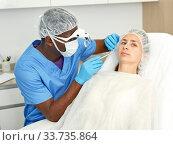 Dermatologist male preparing woman client before aesthetic facial procedure. Стоковое фото, фотограф Яков Филимонов / Фотобанк Лори