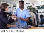 Купить «Laundry worker taking clothes from female client», фото № 33735872, снято 15 января 2019 г. (c) Яков Филимонов / Фотобанк Лори