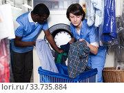 Купить «Laundry workers loading washing machine», фото № 33735884, снято 15 января 2019 г. (c) Яков Филимонов / Фотобанк Лори
