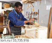 Купить «Craftsman restoring old chest of drawers», фото № 33735916, снято 2 февраля 2019 г. (c) Яков Филимонов / Фотобанк Лори