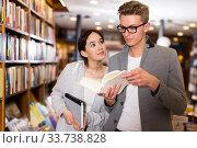 Купить «Glad handsome man and girl choosing books», фото № 33738828, снято 18 января 2018 г. (c) Яков Филимонов / Фотобанк Лори