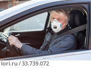 Купить «Dust facial mask is on elder man face while driving a car, Caucasian driver inside a vehicle», фото № 33739072, снято 10 мая 2020 г. (c) Кекяляйнен Андрей / Фотобанк Лори