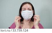 Женщина надевает одноразовую медицинскую маску на лицо. Стоковое видео, видеограф Кекяляйнен Андрей / Фотобанк Лори