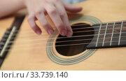 Купить «Hand pluck the strings and fretboard of a yellow acoustic guitar, close up view», видеоролик № 33739140, снято 2 марта 2020 г. (c) Кекяляйнен Андрей / Фотобанк Лори